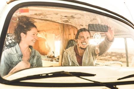 Foto de Indie couple ready for roadtrip on oldtimer mini van transport - Travel lifestyle concept with young hippie people having fun traveling on minivan adventure trip - Warm bright filter - Imagen libre de derechos