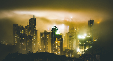 Photo for Hong Kong skyline from Victoria Peak on a foggy misty night - Wandelrust travel concept around south east asia capital cities - Warm dramatic intense filter - Royalty Free Image