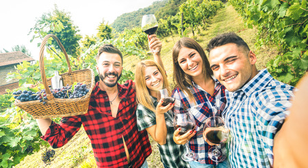 Foto de Young friends having fun taking selfie at winery vineyard outdoor - Friendship concept on happy people enjoying harvest together at farm house - Red wine bio production experience - Azure vivid filter - Imagen libre de derechos