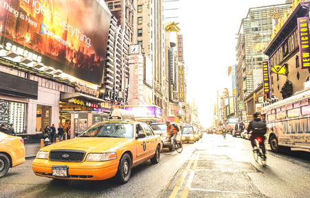 Foto de NEW YORK - MARCH 27, 2015: yellow taxi cab and everyday life near Times Square in Manhattan downtown before sunset - Intersection of 7th Avenue with 42nd Street - Warm sunshine filtered color tones - Imagen libre de derechos