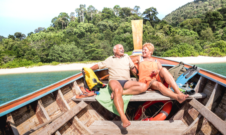 Photo pour Senior couple vacationer relaxing at island hopping tour after beach exploration during snorkel boat trip in Thailand - Active elderly and travel concept on tour around world - Warm day bright filter - image libre de droit