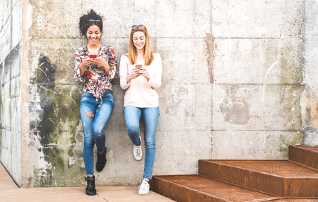 Photo pour Happy girls best friends having fun outdoors with mobile smart phone - Friendship concept with millenial girlfriends on smartphones - Modern female lifestyle with women fashion blogger influencers - image libre de droit