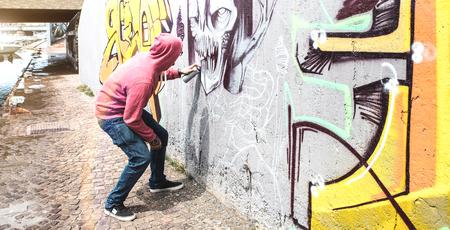 Foto de Street artist painting colorful graffiti on public wall - Modern art concept with urban guy performing and preparing live murales with multi color aerosol spray - Bright retro vintage filter - Imagen libre de derechos