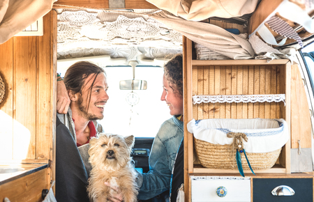 Foto de Indie couple with little dog traveling together on oldtimer mini van transport - Travel lifestyle concept with hipster people on minivan adventure trip having fun in relax moment - Warm retro filter - Imagen libre de derechos