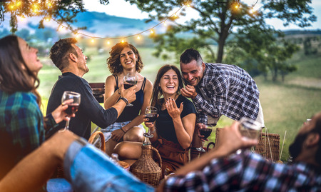 Foto de Young friends having fun at vineyard after sunset - Happy people millennial camping at open air pic nic under bulb lights - Youth friendship concept with guys and girls drinking wine at barbeque party - Imagen libre de derechos