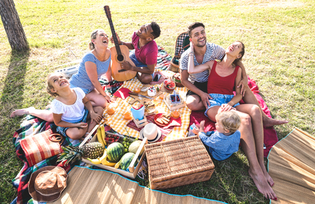 Photo pour High angle top view of happy families having fun with kids at pic nic barbecue party - Multiracial love concept with mixed race people playing with children at public park - Warm retro vintage filter - image libre de droit