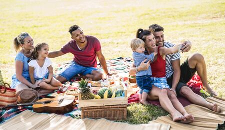 Photo pour Happy multiracial families taking selfie at pic nic garden party - Multicultural joy and love concept with mixed race people having fun together picnic barbecue before sunset - Warm bright filter - image libre de droit
