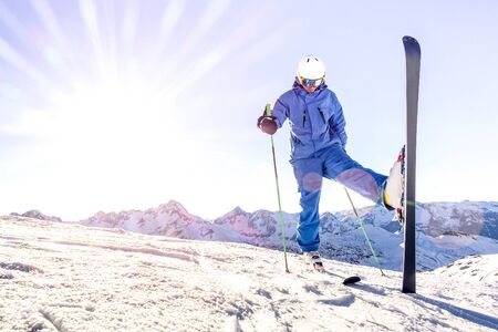 Foto de Young skier on blue uniform at sunset on relax moment in french alps ski resort - Winter adventure and sport concept with professional guy on mountain top ready to ride down - Bright azure filter - Imagen libre de derechos