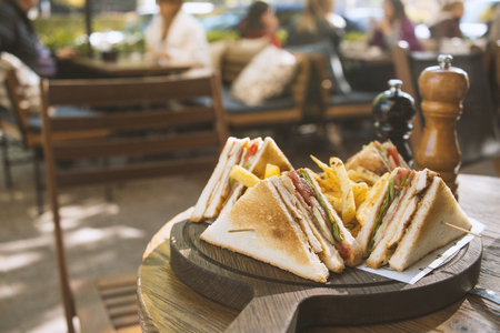 Photo for Club sandwich on wooden board on a table in a cafe - Royalty Free Image