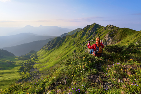 Photo pour Among the wild mountains flowers at the edge of the cliff there is a girl sitting and watching the peaks of mountains at the horizon. Rocky mountains. - image libre de droit