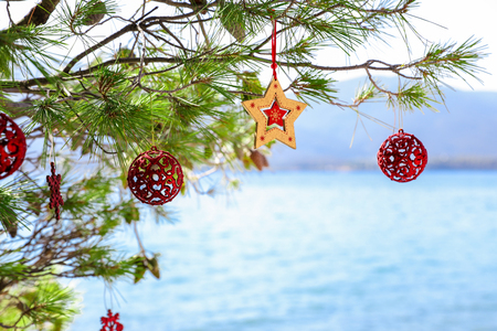 Foto de Christmas decorations hunging on branches of a pine tree growing on the beach of the Aegean sea, New Year holidays by the sea concept. Horizontal. Outdoor. - Imagen libre de derechos