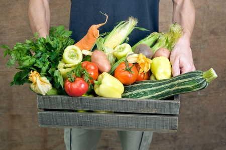 Holding wooden crate with fresh vegetables