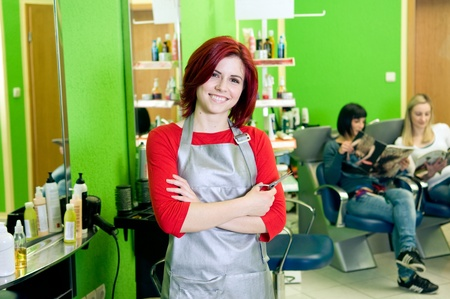 Happy hair salon owner or employee with customers in the background