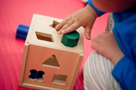 Foto de Toddler playing with wooden shape sorter  - Imagen libre de derechos