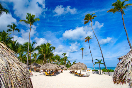 Foto de The White sand of the Dominican beach of Bavaro. Beach chaise lounges under palm shade and blue sky. - Imagen libre de derechos