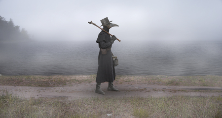 Photo for Medieval era. The plague doctor walks along the road near the misty lake - Royalty Free Image