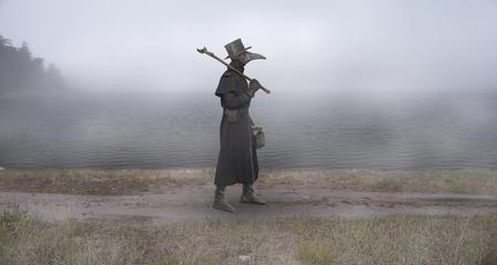 Foto de Medieval era. The plague doctor walks along the road near the misty lake - Imagen libre de derechos