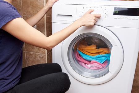 Foto de The girl launches a washing machine with colored things - Imagen libre de derechos
