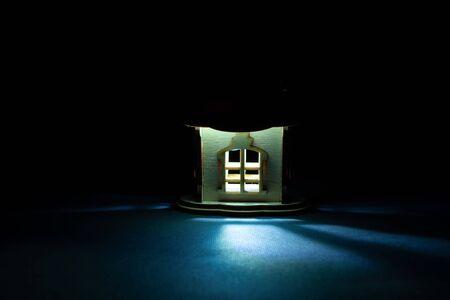 Foto de light comes out of the window of a wooden house in the dark - Imagen libre de derechos