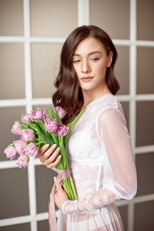 Photo for Cute girl in a white lace dress holding a bouquet of flowers of tulips in her hands a gift for a holiday to the womens day - Royalty Free Image