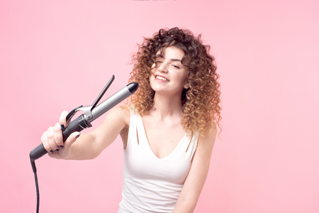 Photo for Charming girl with a smile on her face curly hair in a white T-shirt with curling irons. - Royalty Free Image