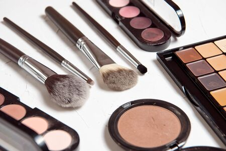 Foto de Professional makeup brushes for the highlighter of the foundation for make-up of the rouge blush coloring on a gray textured background. - Imagen libre de derechos