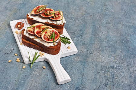 Photo for Vegetarian sandwich with figs, soft cheese, honey, nut and rosemary on white wooden cutting board and blue concrete background with copy space - Royalty Free Image