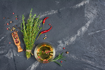Foto de Aromatic or flavored olive oil in glass bowl with spices and herbs as chili peppers and thyme on black marble background with copy space - Imagen libre de derechos