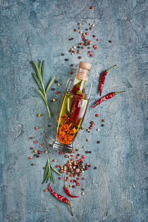 Foto de Aromatic or flavored olive oil in glass bottle with spices and herbs as chili peppers and rosemary on blue concrete background - Imagen libre de derechos