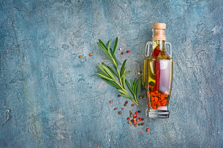 Foto de Aromatic or flavored olive oil in glass bottle with spices and herbs as chili peppers and rosemary on blue concrete background with copy space - Imagen libre de derechos