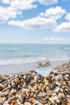 Photo pour Glass round ball on the beach reflects the sea in summer - image libre de droit