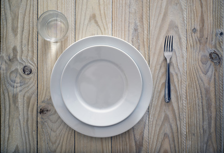 tableware on wooden table. grazing lighting