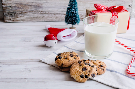Foto per An empty glass of milk with candy and cookies with chocolate chip for Santa on christmas eve on white wooden table. Christmas card. - Immagine Royalty Free