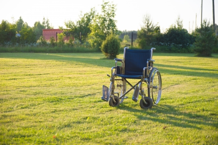 Image of empty wheelchair over green grass