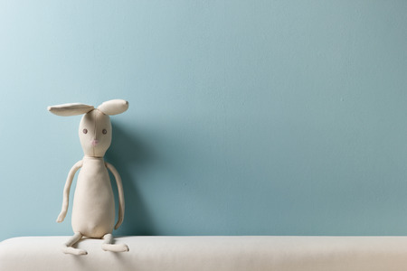 Photo for Home interior. Childhood. Blue background. Toy sitting on a couch. Copy space - Royalty Free Image