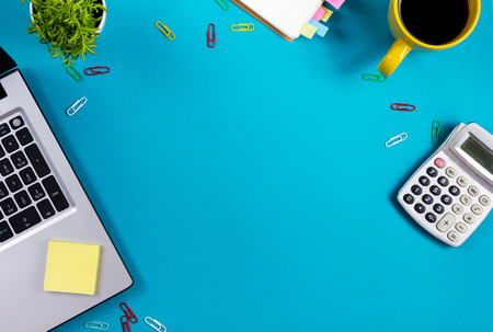 Photo pour Office table desk with set of colorful supplies, white blank note pad, cup, pen, pc, crumpled paper, flower on blue background. Top view and copy space for text. - image libre de droit