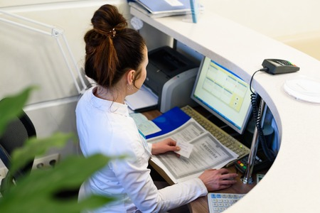 Photo pour Female receptionist working the computer. - image libre de droit