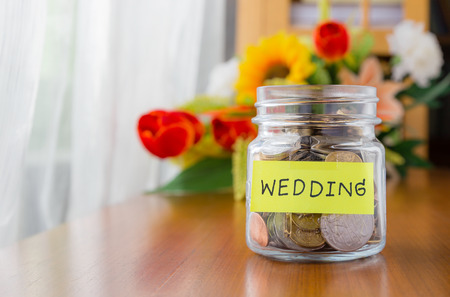 Foto de Many world coins in a money jar with wedding label on jar, beautiful flowers on background - Imagen libre de derechos