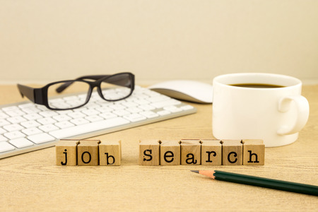 Photo for Job search word on rubber stamps place on table with a cup of coffee, keyboard and glassess, concept for employment - Royalty Free Image