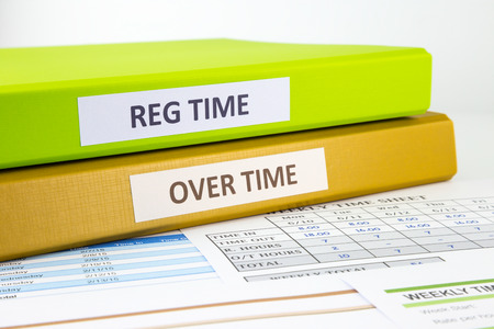 Photo pour Regular time and Over time words on labels, document binders place on employee time sheets - image libre de droit