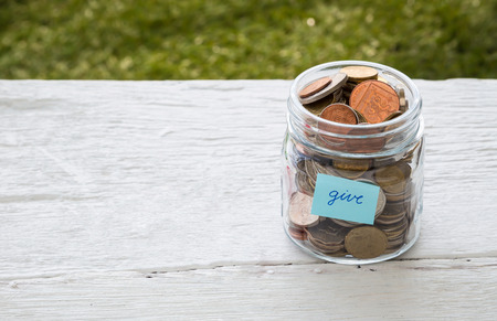 Foto de World coins in money glass jar with blue GIVE word label place on white wood table, blank space for text,  donation and charity concept - Imagen libre de derechos