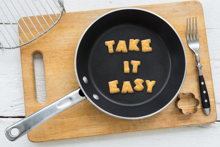 Photo pour Top view of alphabet text collage made of cookies biscuits. Quote TAKE IT EASY putting in frying pan. Other utensils: fork cookie cutter and cutting board putting on white wooden table vintage style image. - image libre de droit