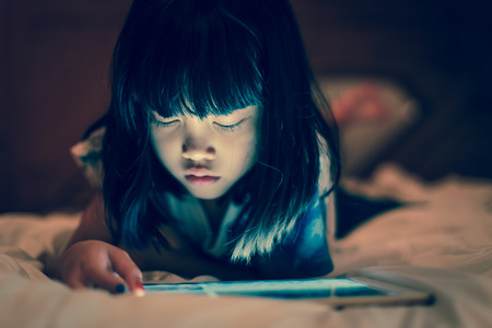 Photo pour Kid using tablet for gaming and online learning while lying on the bed, in dim light bedroom background, screen light reflex on her face. Concept of internet technology, appropriate contents for kids. - image libre de droit