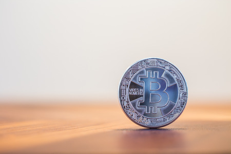Photo for Cryptocurrency symbol sign, focus on silver metal Bitcoin stack on wooden table, blur white background copy space. Decentralized, transfer or exchange digital money through blockchain. - Royalty Free Image