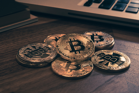Foto de Close up gold Bitcoins on wooden table, notebook in background with dark room light, vintage retro style. Business concepts for blockchain, cryptocurrency, digital money exchange and investment. - Imagen libre de derechos