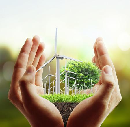 Photo pour Eco power, wind turbines in the hand - image libre de droit