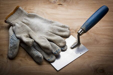 Dirty work gloves on a wooden background