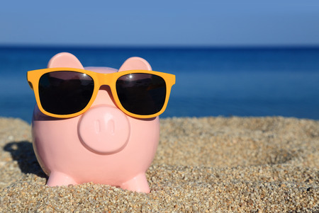 Summer piggy bank with sunglasses on the beach