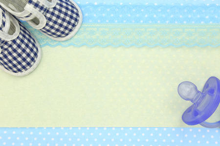 Photo for Baby shoes and blue pacifier on polka dots background with copy space - Royalty Free Image