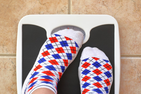 Foto de Woman's feet on bathroom scale. Diet concept - Imagen libre de derechos